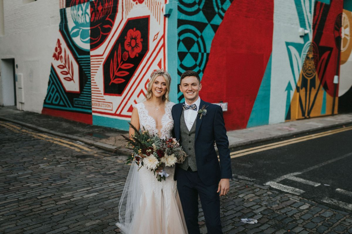 Couple shot in front of Shoreditch street art.